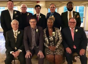 The nine recipients of HEF's 2019 alumni awards pose together at the ceremony